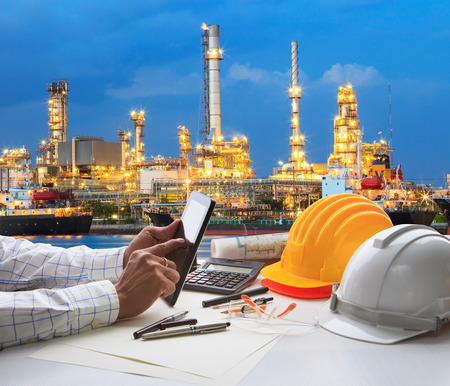 Photo pour engineering working on computer tablet  against beautiful oil refinery background - image libre de droit