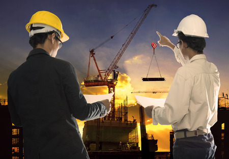 Photo pour two civil engineer working in building construction site against beautiful dusky sky with crane construction - image libre de droit