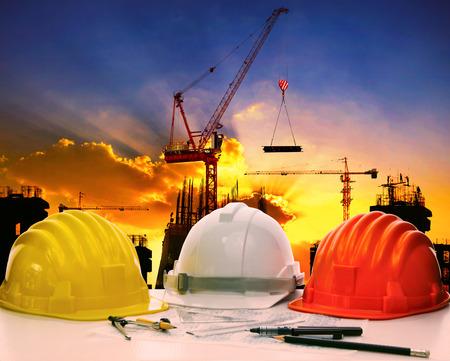 Photo pour safety helmet on civil engineer working table against crane lifting meterial in building construction site - image libre de droit