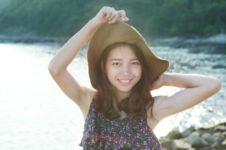 portrait face of beautiful woman wearing wide straw hat standing at sea side eyes looking to camera use for people on vacation and natural beauty of young and teenの写真素材