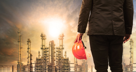 Photo pour engineering man with safety helmet standing in industry estate against sun rising above oil refinery plant - image libre de droit
