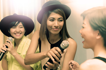 portrait group of asian young woman singing a song in caraoke entertainment room  with happiness emotion and joyful happy face