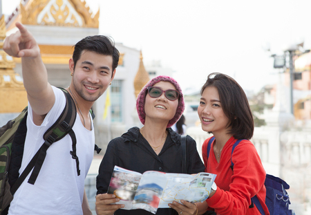 Photo pour traveling man woman and senior tourist holding travel guide book in hand pointing to destination for visiting - image libre de droit