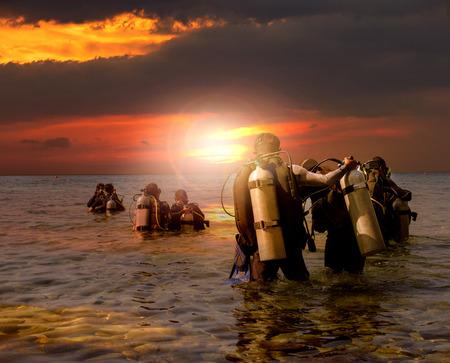 Photo pour group of scuba diving preparing to night diving at sea side against beautiful sun set sky - image libre de droit