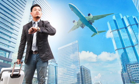 Photo pour business man and belonging luggage watching to sky and hand watch against high building skyscrapers and passenger plane flying above use for aircraft ,air transportation ,traveling of people theme - image libre de droit