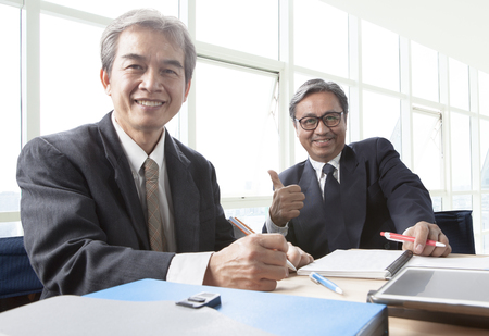 Foto per two of asian business man toothy smiling face ,relaxing in office life - Immagine Royalty Free