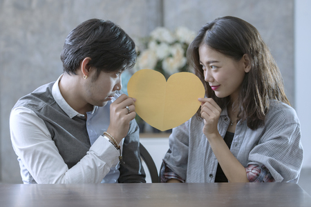 Foto de couples of asian man and woman holding heart shape paper cut with happiness emotion ,peple love conceptual - Imagen libre de derechos