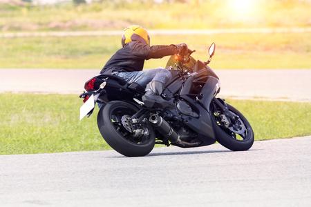 Foto de young man riding motorcycle in asphalt road curve wearing full safety suit - Imagen libre de derechos