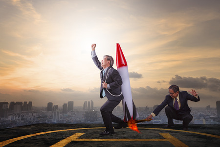 Foto per two business man playing rocket toy on high building roof with sky scraper background abstract for successful business partner - Immagine Royalty Free
