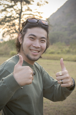 portrait of asian hipster man toothy smiling face with happiness emotion and feeling good with hand sign