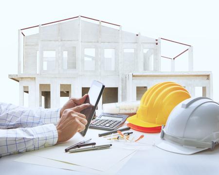 Photo pour architect working table with house construction background - image libre de droit
