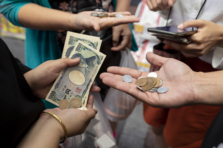 Photo pour tourist hand and japanese yen banknote in traveling shopping area - image libre de droit