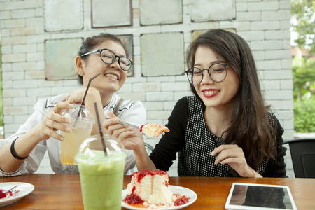 Photo pour two asian woman happiness emotion eating strawberry cheese cake in cafe - image libre de droit