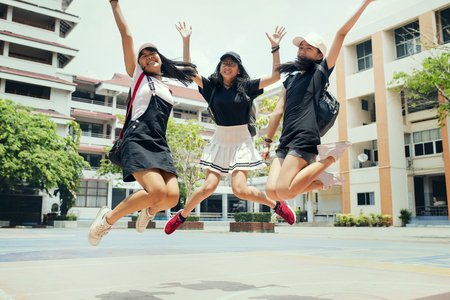 Photo pour three asian teenager jumping mid air with happiness emotion against school building background - image libre de droit