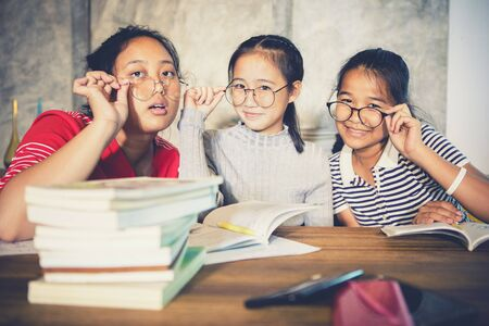 Photo pour cheerful asian teenager wearing eye glasses with school book in home living room - image libre de droit