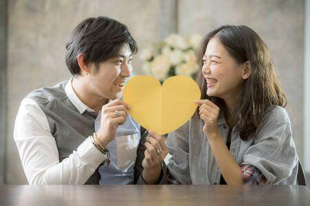 Photo pour couples of asian man and woman holding heart shape paper cut with happiness emotion ,people love conceptual - image libre de droit