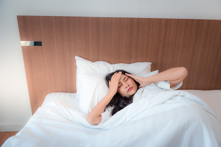 Pretty asian woman feeling headache after waked up in her's bedroom., Health and medical concept