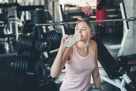 Photo for Beautiful Fitness Woman is Drinking Water From Bottle After Working Out in Gym, Portrait of Athletic Pretty Woman is Drinking Water After Exercising in Front of Bodybuilder Machine, Sport and Healthy. - Royalty Free Image