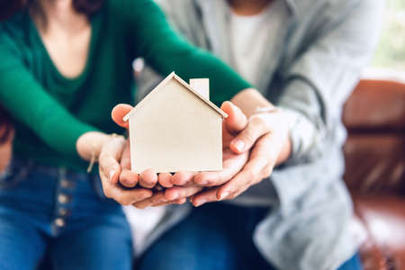 Photo pour Couple Hands Holding Housing Model for Future Real Estate Saving, People Hand Joint to Protection Home Property Togetherness. House Insurance and Residential Loan Investment Concept. - image libre de droit