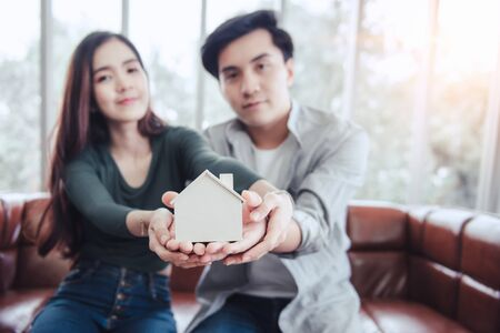 Photo pour Couple Hands Holding Housing Model for Future Real Estate Saving, Attractive Asian Couple Hand Joint to Protection Home Property Togetherness. House Insurance and Residential Loan Investment Concept. - image libre de droit