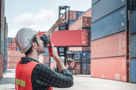 Photo for Container Logistics Shipping Management of Transportation Industry, Transport Engineer Managing Control Via Walkie Talkie in Containers Shipyard. Business Cargo Ship Import/Export Factory Logistic. - Royalty Free Image