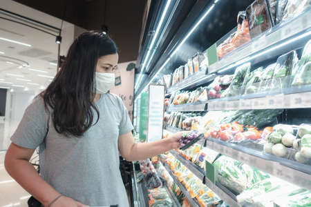 Foto für Customer Asian Woman Wearing Face Mask With Shopping Cart in Supermarket Department Store Shop While Choosing and Looking Vegetables on Shelf During Covid-19 Pandemic. Coronavirus Covid Situation - Lizenzfreies Bild