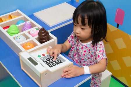 Foto de Asian Chinese little girl role-playing at ice cream store. - Imagen libre de derechos