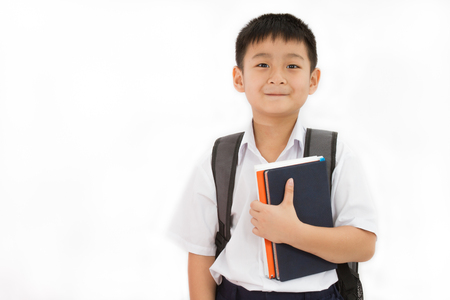 Foto de Asian Little School Boy Holding Books with Backpack on White Background - Imagen libre de derechos