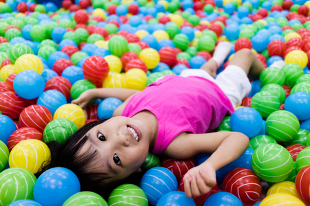 Foto de Asian Little Chinese Girl Playing with Colorful Plastic Balls in Indoor Playground - Imagen libre de derechos