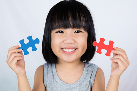 Photo for Asian Little Chinese Girl Playing Colorful Puzzle in isolated White Background - Royalty Free Image