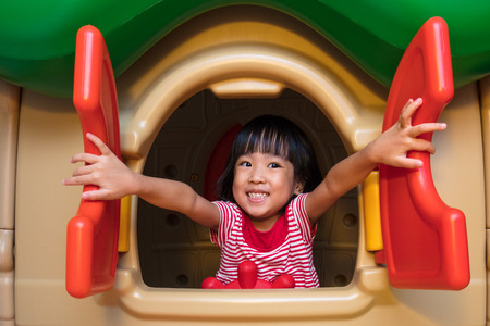Foto de Asian Chinese little girl playing in toy house at indoor playground. - Imagen libre de derechos