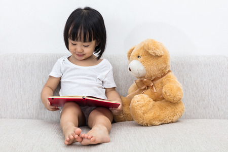 Photo pour Asian Chinese little girl reading book with teddy bear on the sofa in the living room. - image libre de droit