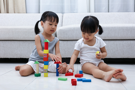 Photo pour Asian Chinese little sisters playing blocks on the floor in the living room at home. - image libre de droit