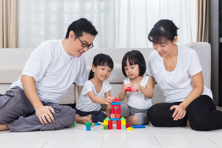 Photo for Asian Chinese parents and daughters playing blocks on the floor in the living room at home. - Royalty Free Image
