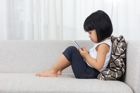 Foto de Asian Chinese little girl lying on the sofa with mobile phone in the living room at home. - Imagen libre de derechos