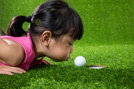 Photo pour Asian Chinese little girl lying on grass and blowing the ball into a hole - image libre de droit