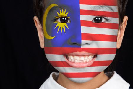 Asian chinese little girl with Malaysian flag on the face in isolated black background
