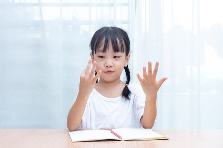 Photo pour Asian little Chinese Girl doing mathematics by counting fingers at home - image libre de droit