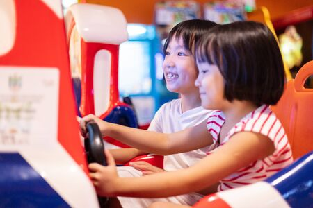 Photo pour Asian Little Chinese Sisters playing at amusement indoor - image libre de droit