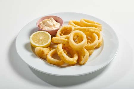 Foto de Plate of fried sliced squid with mayonnaise sauce, lemon on white background - Imagen libre de derechos