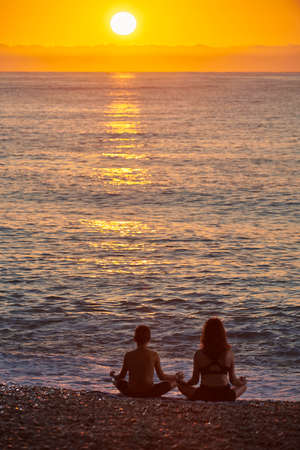Foto de Single mother on the beach with son at sunrise, Happy family at sunrise on a summer day at the beach, family enjoying vacation. - Imagen libre de derechos