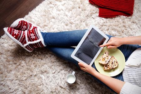 Foto de Woman with a tablet eating traditional Christmas cookies - Imagen libre de derechos