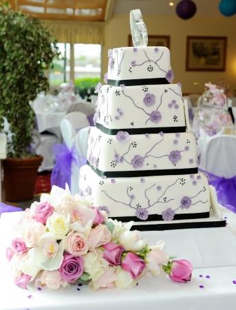Purple wedding cake with brides bouquet at reception