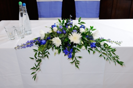 Wedding ceremony table decorated with blue and white flowers