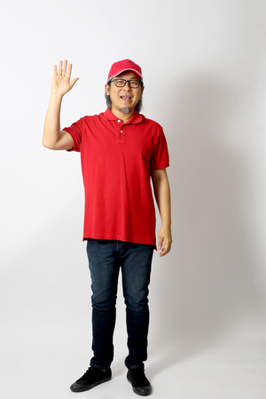 The Asian man dressed red polo shirt with red cap standing on the white background.