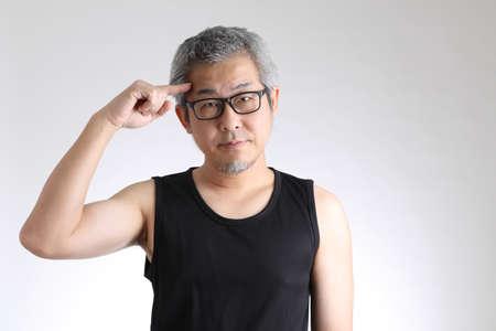 Photo pour The elder Asian man in sport uniform standing on the white background. - image libre de droit