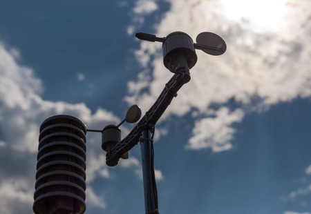 Home weather station on a background of blue sky. Measurement of temperature, humidity and wind direction