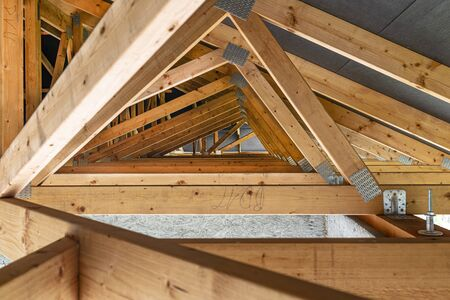 Photo pour Roof trusses covered with a membrane on a detached house under construction, view from the inside, visible roof elements and truss plates. - image libre de droit