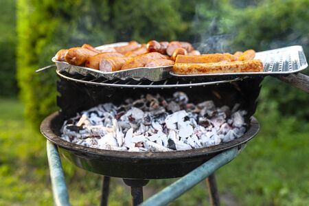 Photo pour The seasoned and incised sausage lying on an aluminum tray, on a managing grill, in the home garden. - image libre de droit