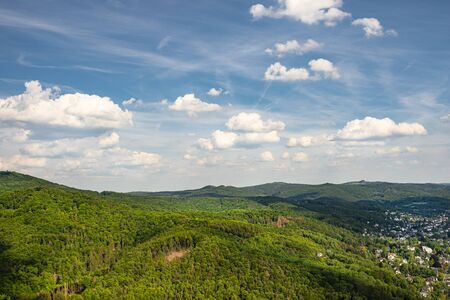 Photo pour Landscape of green forest on the hills in summer with blue sky and white clouds. Photo taken in West Germany. - image libre de droit